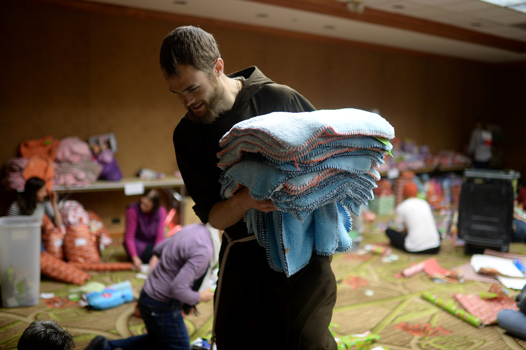 """. DENVER, CO. DECEMBER 21: Brother Donald is gathering the blankets during the annual Father Woody Christmas Party in Denver, Colorado December 21, 2013. In advance of handing out 5,000 gifts, volunteers are doing a \""""wrapping party\"""" at the Sheraton Denver Downtown Hotel. (Photo by Hyoung Chang/The Denver Post)"""