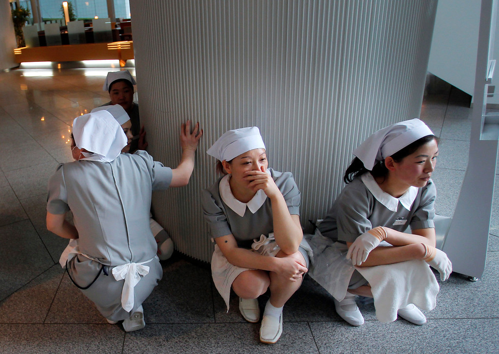 . Hotel employees squat down in horror at the hotel\'s entrance in Tokyo after a strong earthquake hit Japan Friday, March 11, 2011. (AP Photo/Itsuo Inouye)