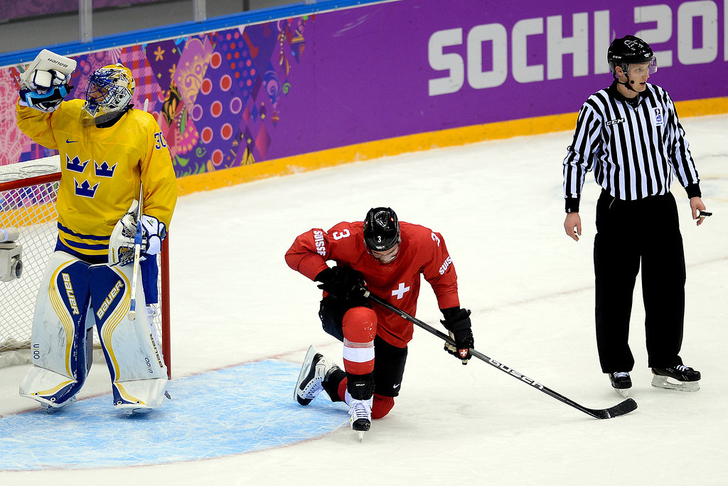 . Switzerland\'s Julien Vauclair kneels on the ice after being taken down by Sweden\'s Jimmie Ericsson during the action at Bolshoy Arena. Sochi 2014 Winter Olympics on Friday, February 14, 2014. (Photo by AAron Ontiveroz/The Denver Post)