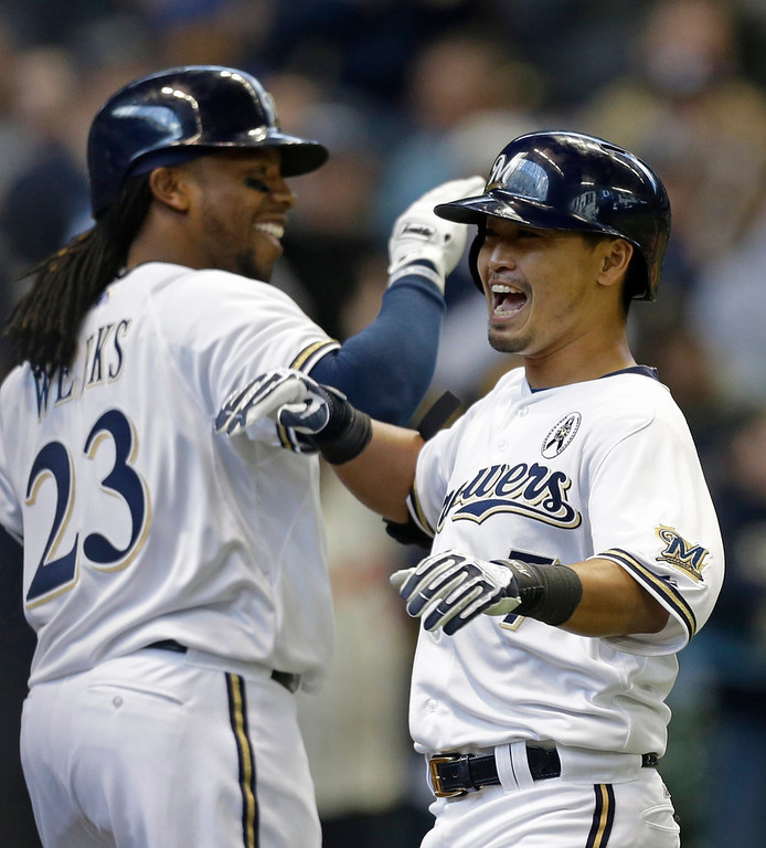 . Milwaukee Brewers\' Norichika Aoki, right, reacts with Rickie Weeks(23) after Aoki\'s home run against the Colorado Rockies in the third inning of an Opening Day baseball game  Monday, April 1, 2013, in Milwaukee. (AP Photo/Jeffrey Phelps)