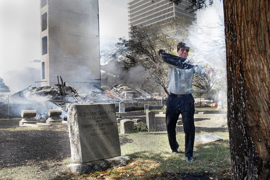 . Concerned citizen Craig Guidry splashes water on a smoldering cypress tree in Magnolia Cemetery as  five-alarm fire burn at a nearby construction site Tuesday, March 25, 2014, in Houston. (AP Photo/Houston Chronicle, Eric Kayne)