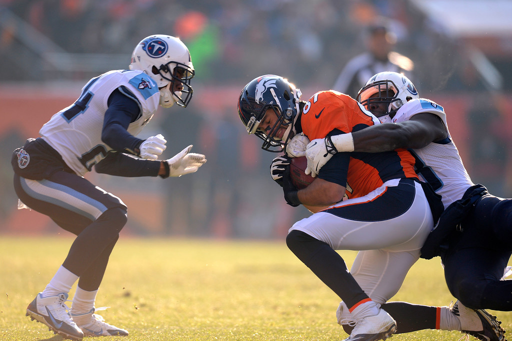 . DENVER, CO - DECEMBER 08: Denver Broncos wide receiver Eric Decker (87) is tackled by Tennessee Titans middle linebacker Moise Fokou (53) and Tennessee Titans cornerback Coty Sensabaugh (24). The Denver Broncos take on the Tennessee Titans at Sports Authority Field at Mile High in Denver on December 8, 2013. (Photo by John Leyba/The Denver Post)