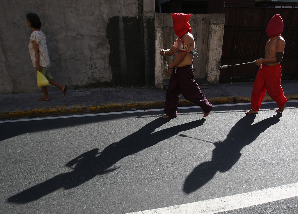 . Filipino hooded penitents walk along the street during Maundy Thursday rituals to atone for sins, in suburban Mandaluyong, east of Manila, Philippines, on Thursday, March 28, 2013. The ritual is frowned upon by church leaders in this predominantly Roman Catholic country. (AP Photo/Aaron Favila)