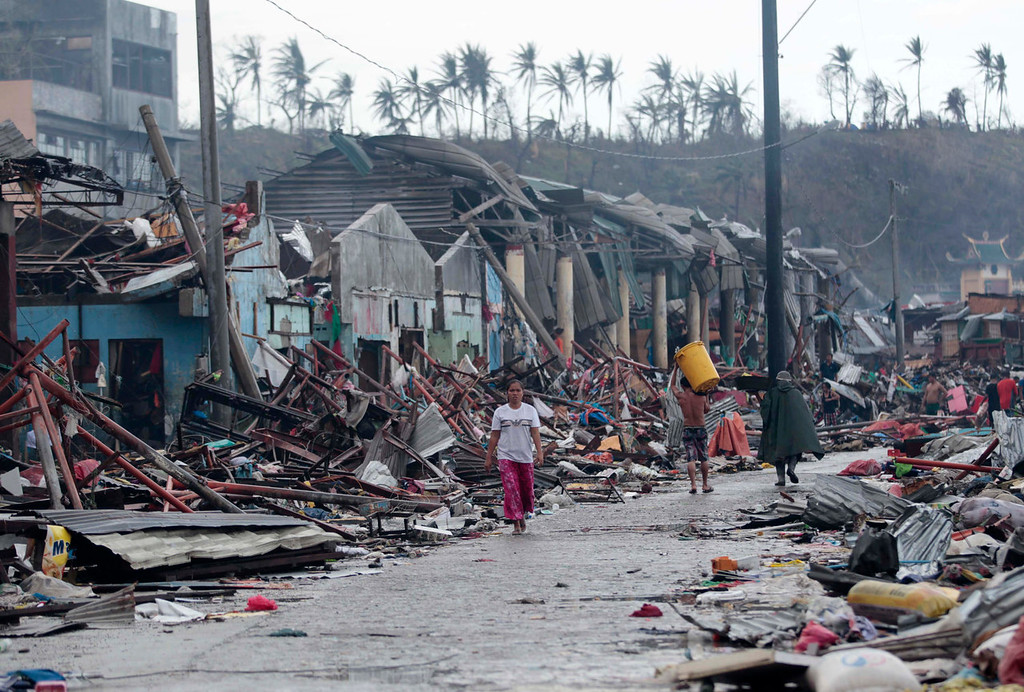 . Residents walk past damaged structures caused by typhoon Haiyan,  in Tacloban city, Leyte province central Philippines on Sunday, Nov. 10, 2013. Haiyan, one of the most powerful typhoons ever recorded, slammed into central Philippine provinces Friday leaving a wide swath of destruction and scores of people dead.  (AP Photo/Aaron Favila)
