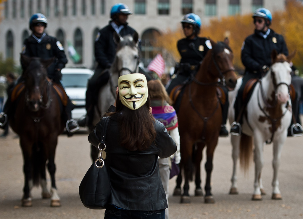 . A demonstrator and supporter of the group Anonymous, passes in front of a group of mounted police during a march in protest against corrupt governments and corporations in front of the White House in Washington, DC, November 5, 2013, as part of a Million Mask March of similar rallies around the world on Guy Fawkes Day. AFP PHOTO/MLADEN  ANTONOV/AFP/Getty Images