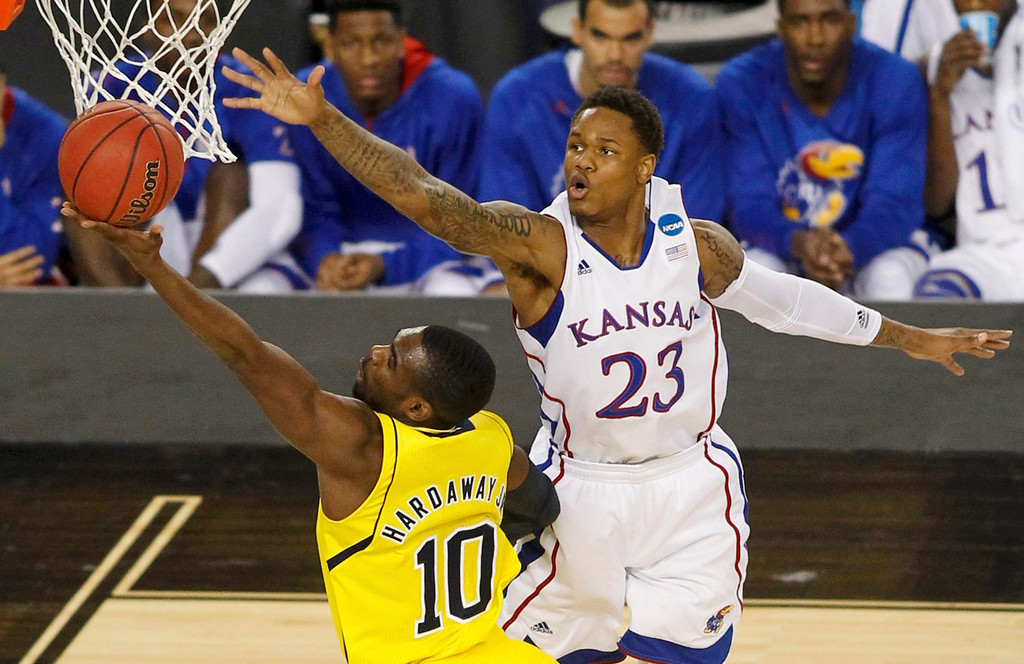 . Kansas Jayhawks guard Ben McLemore (R) reaches for the ball as Michigan Wolverines guard Tim Hardaway Jr. shoots during the first half in their South Regional NCAA mens basketball game in Arlington, Texas March 29, 2013. REUTERS/Tim Sharp