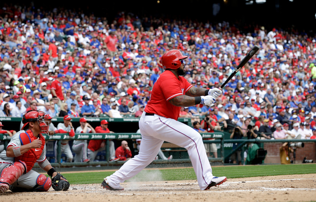 . Texas Rangers\' Prince Fielder flies out to right during the fourth inning of an opening day baseball game against the Philadelphia Phillies at Globe Life Park, Monday, March 31, 2014, in Arlington, Texas.  (AP Photo/Tony Gutierrez)