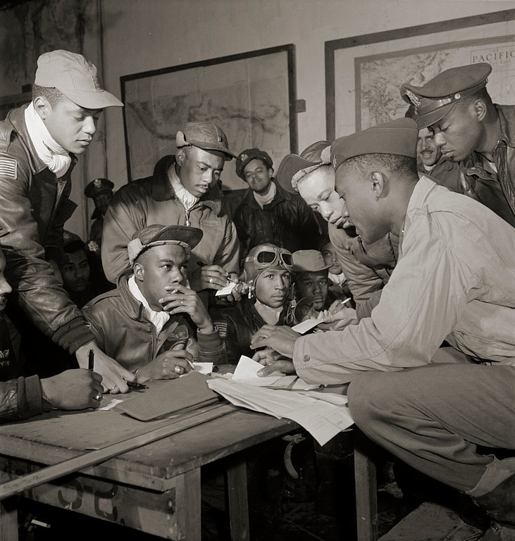 """. The Tuskegee Airmen were the first African-American military aviators in the United States armed forces. Several Tuskegee airmen at Ramitelli, Italy, March, 1945. Front row, left to right: unidentified airman; Jimmie D. Wheeler (with goggles); Emile G. Clifton (cloth cap) San Francisco, CA, Class 44-B. Standing left to right: Ronald W. Reeves (cloth cap) Washington, DC, Class 44-G; Hiram Mann (leather cap); Joseph L. \""""Joe\"""" Chineworth (wheel cap) Memphis, TN, Class 44-E; Elwood T. Driver? Los Angeles, CA, Class 44-A; Edward \""""Ed\"""" Thomas (partial view); Woodrow W. Crockett (wheel cap); at Ramitelli, Italy, March 1945. (Source: Tuskegee Airmen 332nd Fighter Group pilots.) Toni Frissell, photographer. Library of Congress"""