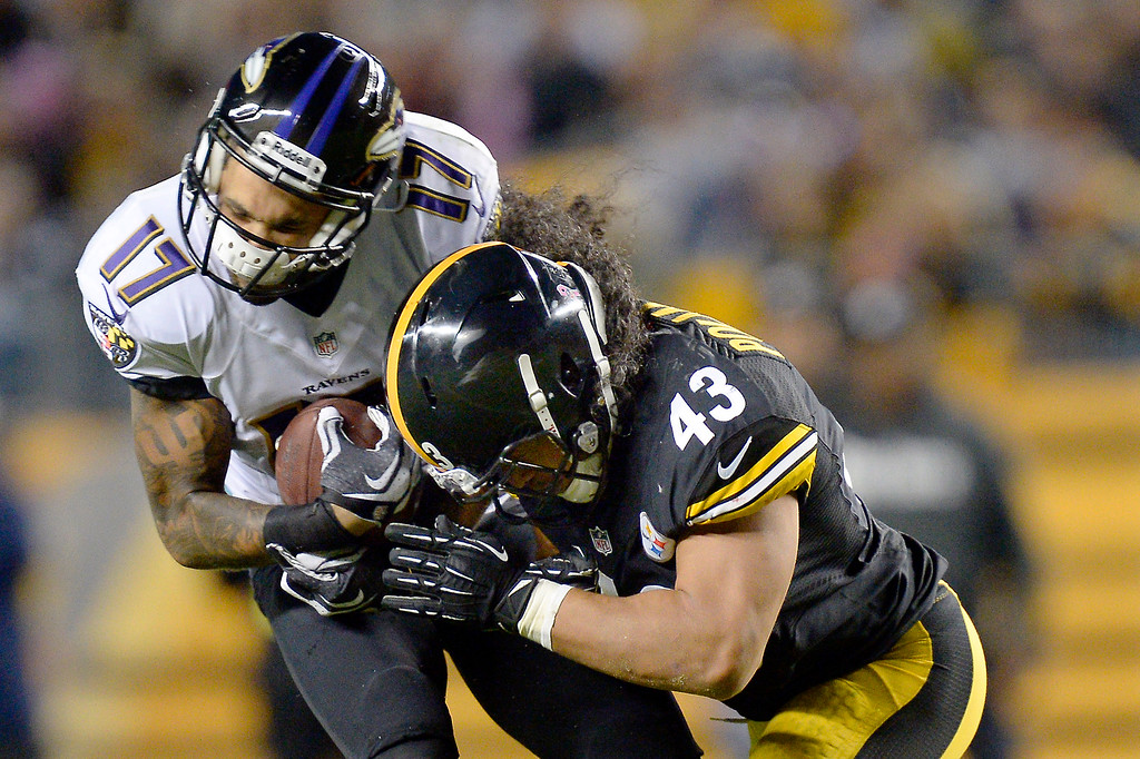 . Pittsburgh Steelers strong safety Troy Polamalu (43) hits Baltimore Ravens wide receiver Tandon Doss after making a catch in the fourth quarter of an NFL football game on Sunday, Oct. 20, 2013, in Pittsburgh. Doss held on to the ball. The Steelers won 19-16. (AP Photo/Don Wright)