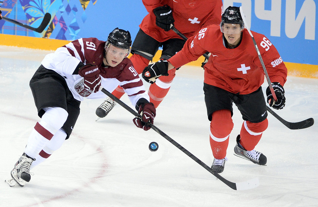 . Latvia\'s Ronalds Kenins (L) vies with Switzerland\'s Damien Brunner during the Men\'s Ice Hockey match between Latvia and Switzerland at the Shayba arena during the Sochi Winter Olympics on February 12, 2014. ANDREJ ISAKOVIC/AFP/Getty Images