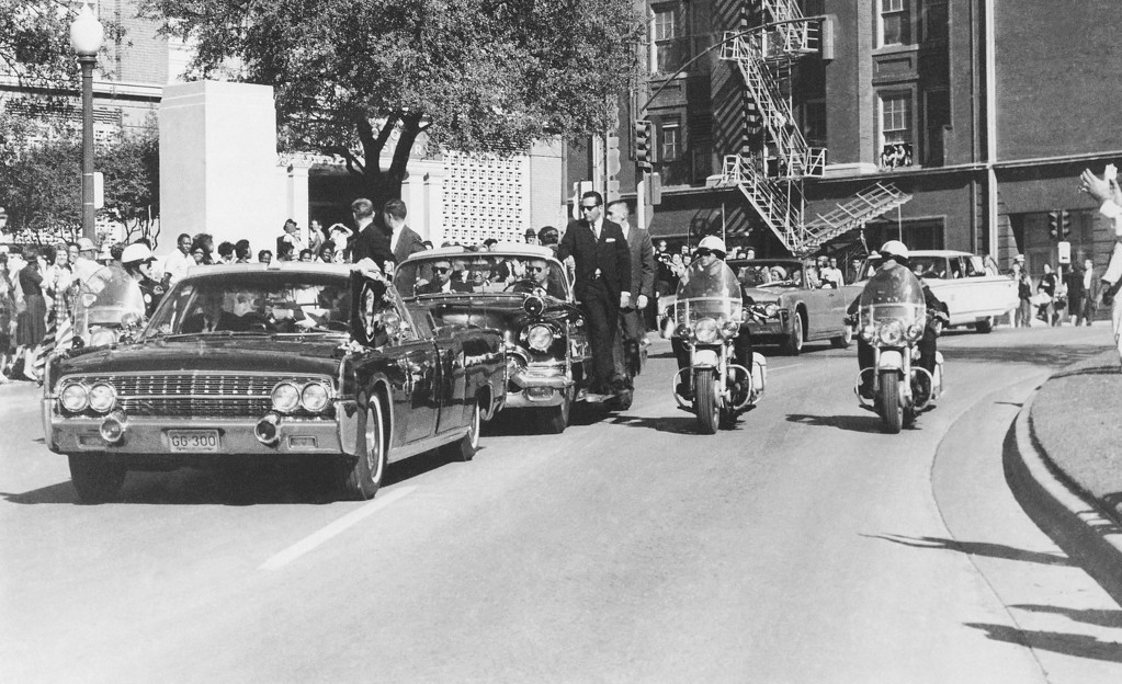 . Seen through the limousine\'s windshield as the car  proceeds along Elm Street past the Texas School Book Depository, Kennedy appears to raise his hand toward his head within seconds of being fatally shot. Jacqueline Kennedy holds the president\'s forearm in an effort to aid him. Texas Gov. John Connally, who was in the seat in front of the Kennedys, was woundedt. James W. Altgens, Associated Press file