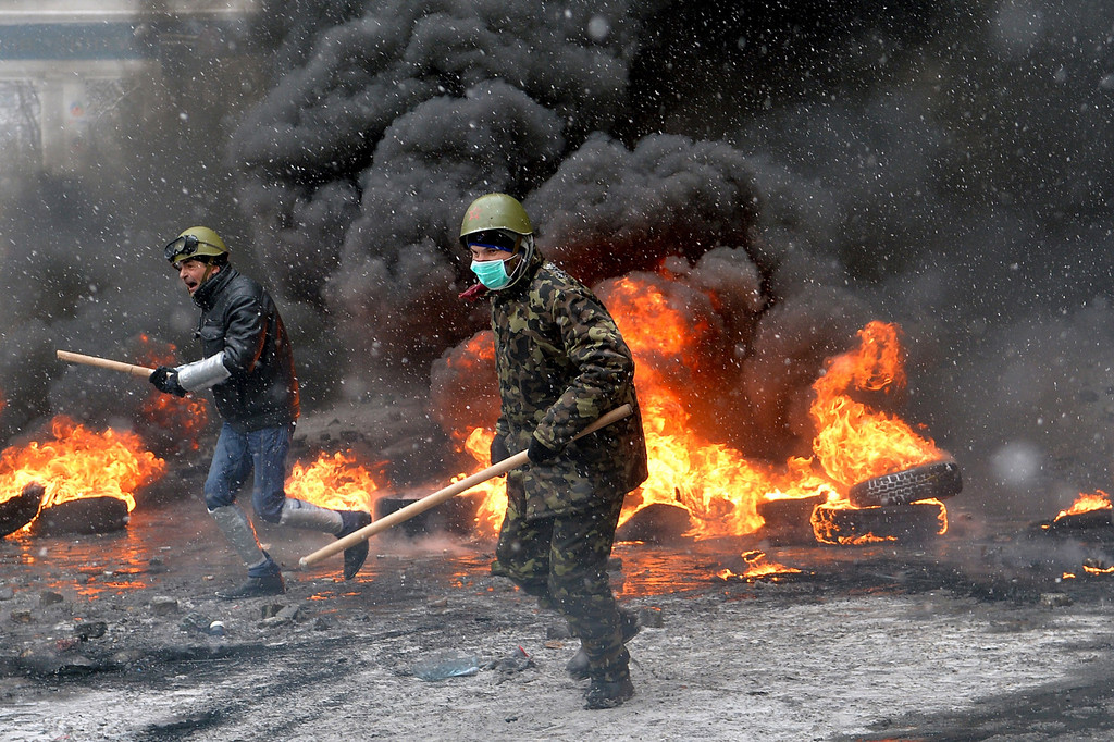 . Protestors clash with police in the center of Kiev on January 22, 2014. At least two activists were shot dead today as Ukrainian police stormed protesters\' barricades in Kiev, the first fatalities in two months of anti-government protests. Pitched battles raged in the centre of the Ukrainian capital as protesters hurled stones at police and the security forces responded with tear gas and rubber bullets. AFP PHOTO / SERGEI SUPINSKY/AFP/Getty Images
