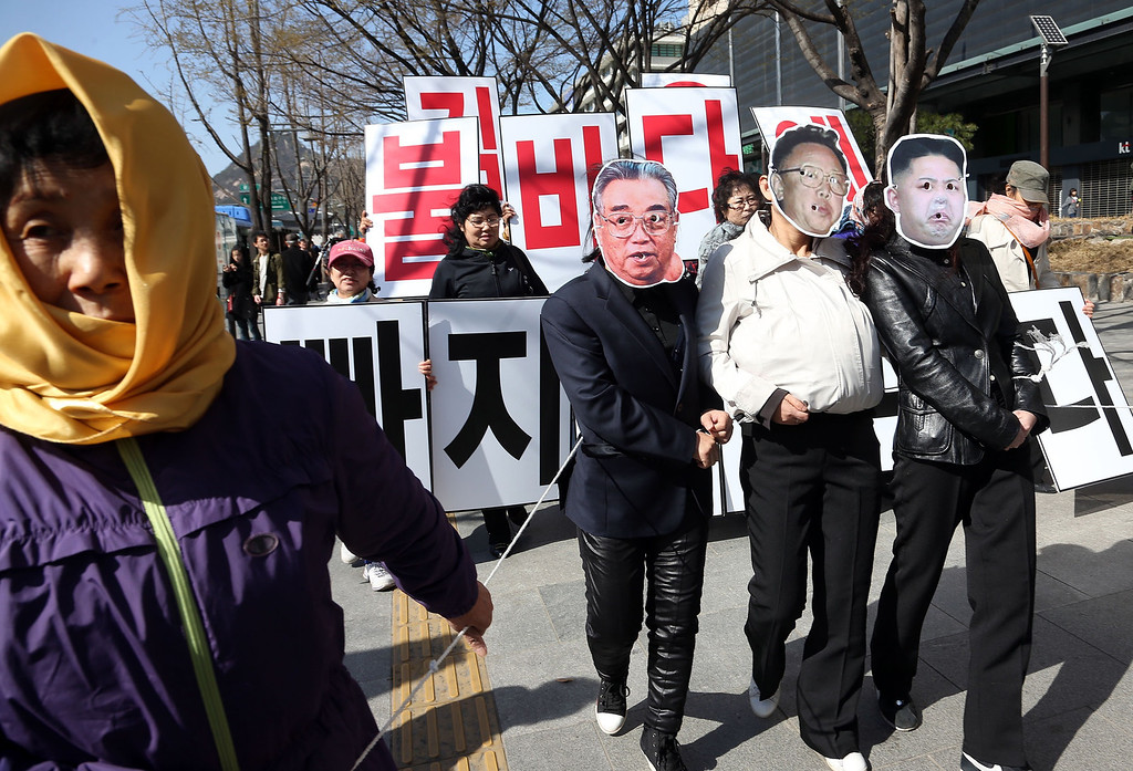 """. Activists wear masks resembling (L-R) late North Korean founder Kim Il-Sung, late leader Kim Jong-Il and current leader Kim Jong-Un during an anti-North Korea protest held by a civic group which consists of former female North Korean defectors living in the South, in Seoul April 14, 2013. Kim Il-Sung\'s 101st birthday falls on April 15, 2013. Korean characters in background read,\""""Kim Jong-Un, it is you who will fall into the sea of fire\"""".          REUTERS/Lee Ji-Eun/Yonhap"""