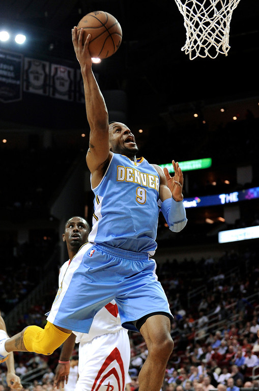 . Denver Nuggets\' Andre Iguodala (9) goes up for 2 points as Houston Rockets\' Patrick Patterson, left, watches in the first half of an NBA basketball game Wednesday, Jan. 23, 2013, in Houston. (AP Photo/Pat Sullivan)