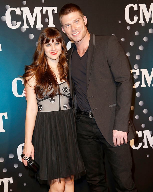 """. Actor Chris Carmack, right, of ABC\'s \""""Nashville\"""" and actress producer Aubrey Peeples pose on the red carpet at the CMT \""""Artists of the Year\"""" event at Bridgestone Arena, on Tuesday, December 3, 2013, in Nashville, Tenn. (Photo by Donn Jones/Invision/AP)"""