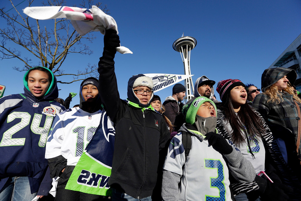 . Seattle Seahawks fans cheer as they wait for the Seahawks\' Super Bowl victory parade to begin Wednesday, Feb. 5, 2014, in Seattle.  (AP Photo/Elaine Thompson)