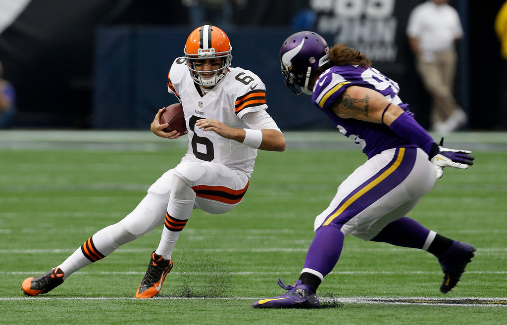 . Cleveland Browns quarterback Brian Hoyer, left, runs from Minnesota Vikings defensive end Brian Robison during the first half of an NFL football game Sunday, Sept. 22, 2013, in Minneapolis. (AP Photo/Ann Heisenfelt)
