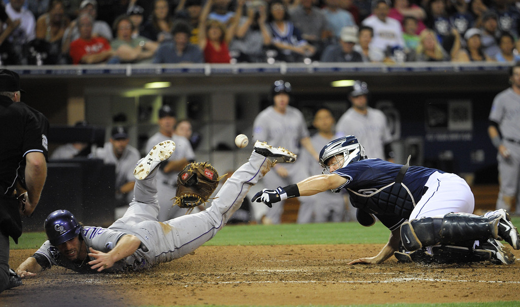 . SAN DIEGO, CA - SEPTEMBER 7:  Nick Hundley #4 of the San Diego Padres loses his glove and the ball as Charlie Culberson #23 of the Colorado Rockies scores  during the eighth inning of a baseball game at Petco Park on September 7, 2013 in San Diego, California.  (Photo by Denis Poroy/Getty Images)