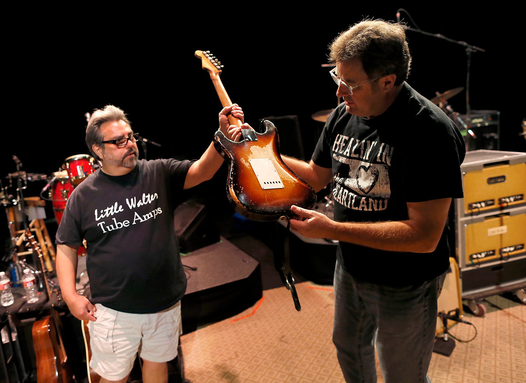 ". Guitar technician Vinnie Garcia hands Country legend Vince Gill his 1957 Fender Stratocaster after a sound check at the Mesa Performing Arts Center, in Mesa, Ariz. on Thursday, Oct. 24, 2013. Garcia, who has been best friends with Gill since the seventh grade, sold Gill his first Stratocaster for $200 and a pair of cowboy boots. Gill says, ""I love the versatility of the guitar as much as anything, no matter what way you want to try to play it, it always responds.\"" (AP Photo/Matt York)"