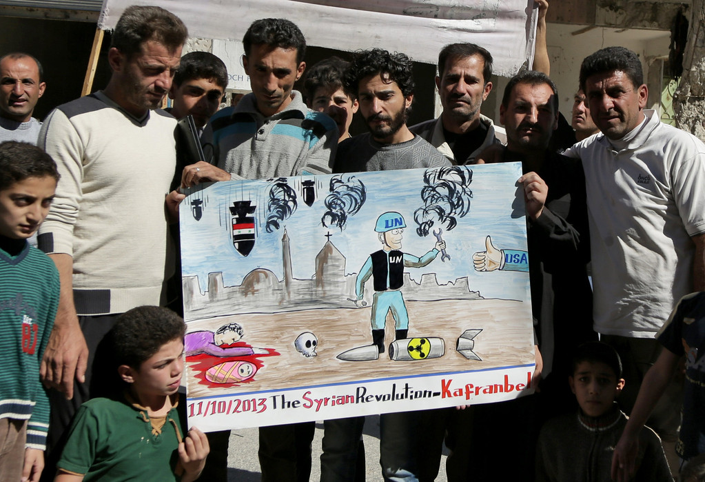 . Syrian anti-government protestors hold a poster depicting a inspector from the Organization for the Prohibition of Chemical Weapons (OPCW) during a demonstration to call for an international action against the Damascus regime on October 11, 2013. The watchdog now overseeing the destruction of Syria\'s chemical arsenal won the Nobel Peace Prize for its efforts to rid the world of the devastating weapons.  MEZAR MATAR/AFP/Getty Images