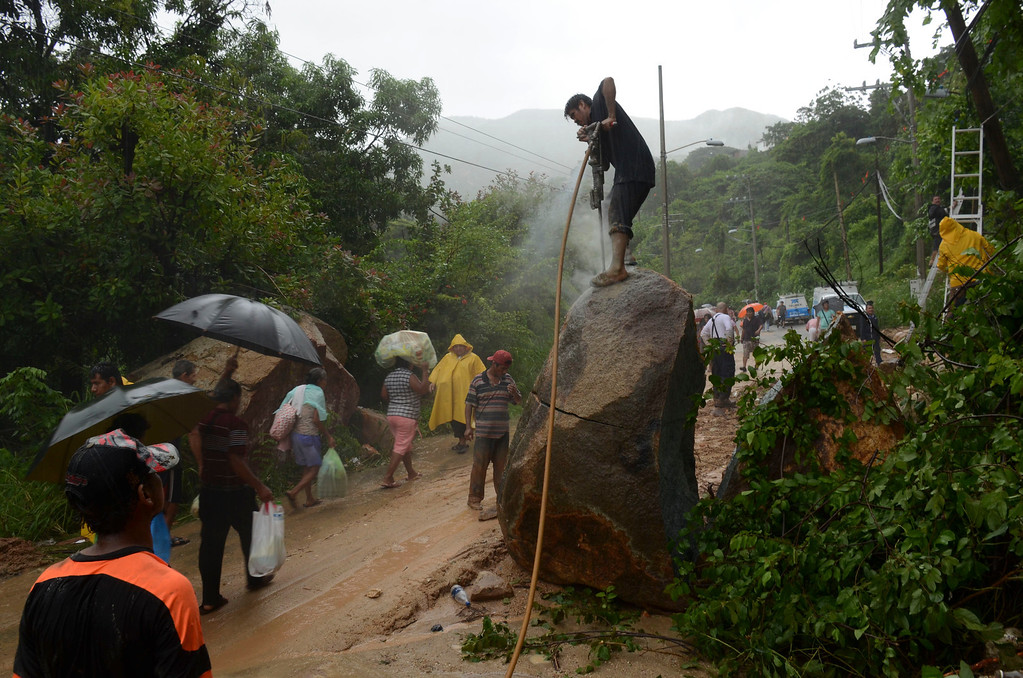 . A man works to break apart a boulder with a jackhammer as people make their way on foot, near a road, that was cut off after heavy rains brought on by Tropical Storm Manuel triggered a landslide, on the outskirts of Acapulco, Mexico, Monday, Sept. 16, 2013. Tropical Storm Ingrid and remnants of Tropical Storm Manuel drenched Mexico\'s Gulf and Pacific coasts, flooding towns and cities in a national emergency that federal authorities say has caused at least 34 deaths. (AP Photo/Bernandino Hernandez)