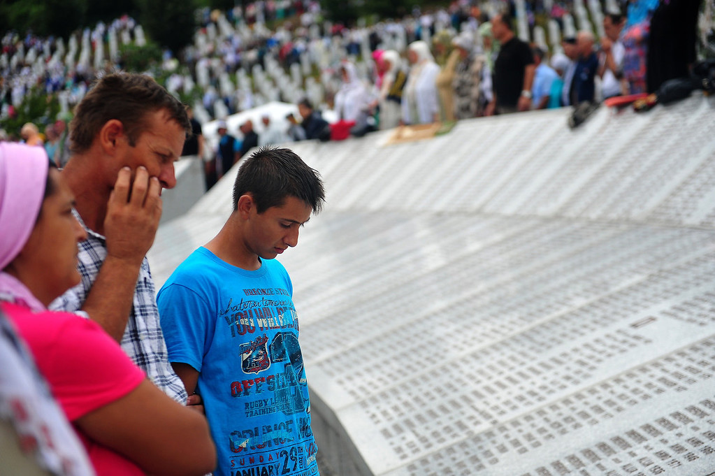 . Bosnian Muslims search for the names of their relatives killed during Srebrenica 1995 massacre, on a monument at a memorial cemetery in the village of Potocari near the eastern Bosnian town of Srebrenica on July 11, 2013. Bosnia buried 409 victims of the Srebrenica massacre on July 11, including a newborn baby, on the 18th anniversary of the worst slaughter in post-war Europe. More than 15,000 people travelled to Potocari, near Srebrenica to attend the mass funeral of victims whose remains were found in mass graves and only identified almost two decades after the 1995 killing.  ELVIS BARUKCIC/AFP/Getty Images