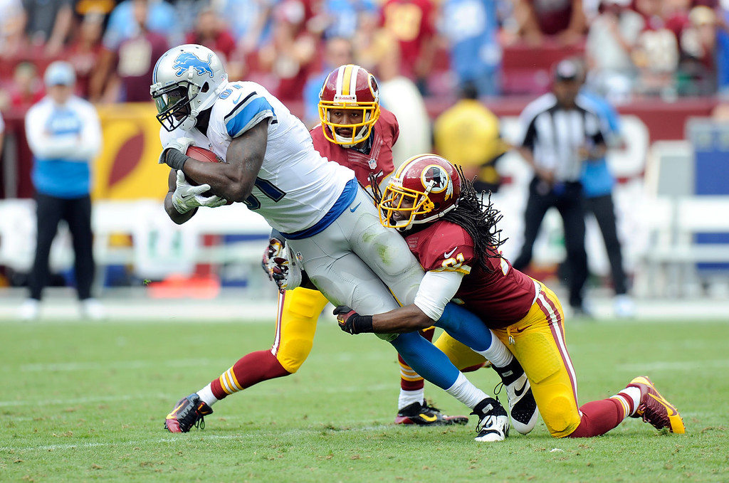 . LANDOVER, MD - SEPTEMBER 22:  Brandon Meriweather #31 and Josh Wilson #26 of the Washington Redskins tackle Calvin Johnson #81 of the Detroit Lions in the second quarter at FedExField on September 22, 2013 in Landover, Maryland.  (Photo by Greg Fiume/Getty Images)
