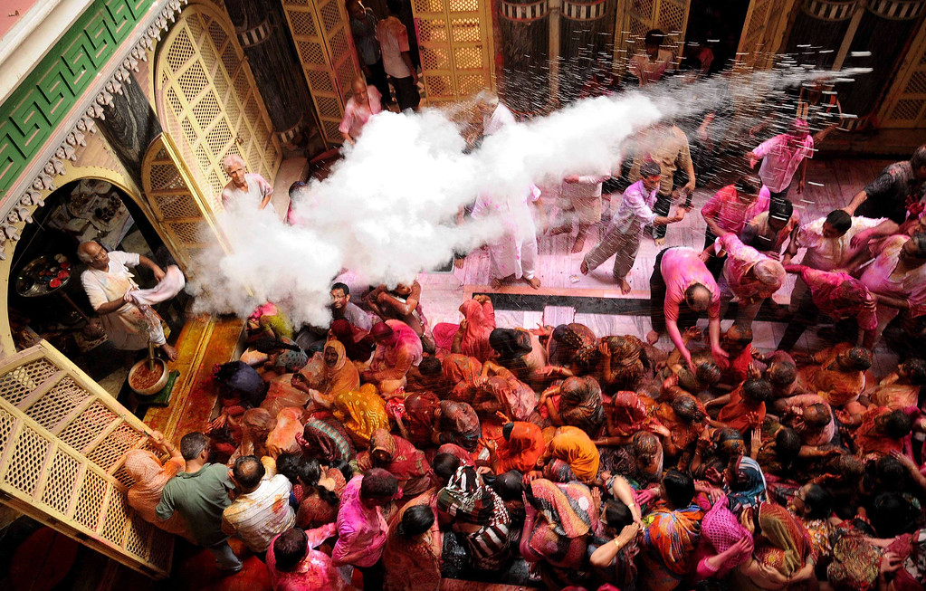 . A Hindu priest throws colored powder over devotees as they celebrate the Holi festival at the Radha Krishna temple in Kolkata on March 17, 2014. Holi, the popular Hindu spring festival of colors is observed in India at the end of the winter season on the last full moon of the lunar month. AFP PHOTO/STRSTRDEL/AFP/Getty Images