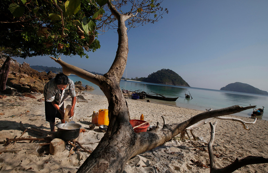 . In this Sunday, Feb. 9, 2014 photo, a woman belonging to Moken tribe, nomads of the sea, cooks food in the shade of a tree on Island 115 in Mergui Archipelago, Myanmar. Isolated for decades by the country�s former military regime and piracy, the Mergui archipelago is thought by scientists to harbor some of the world�s most important marine biodiversity and looms as a lodestone for those eager to experience one of Asia�s last tourism frontiers before, as many fear, it succumbs to the ravages that have befallen many of the continent�s once pristine seascapes. (AP Photo/Altaf Qadri)