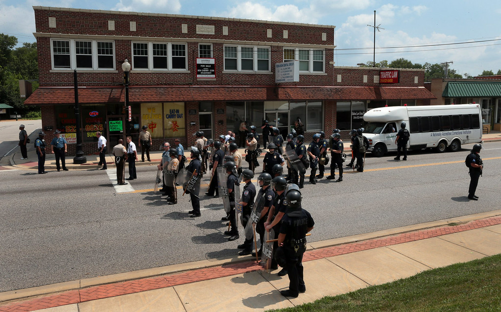 . Riot police officers moved down S. Florissant Road in downtown Ferguson, Mo.,  on Monday, Aug. 11, 2014, as they move demonstrators from the police station after Saturday\'s police shooting of Michael Brown. (AP Photo/St. Louis Post-Dispatch, Robert Cohen)