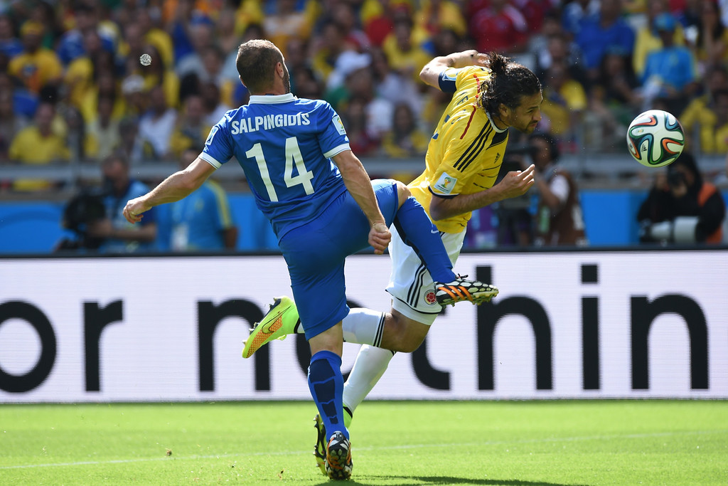. Colombia\'s defender Mario Yepes (R) in action against Greece\'s forward Dimitris Salpingidis during a Group C football match between Colombia and Greece at the Mineirao Arena in Belo Horizonte during the 2014 FIFA World Cup on June 14, 2014.    AFP PHOTO / PEDRO UGARTE