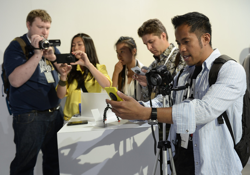 . Members of the press takes  photos after the official  unveiling of  the Nokia Lumia 1020, a Windows Phone with a 41-megapixel camera at a event in New York City on July 11, 2013.  AFP PHOTO / TIMOTHY  CLARY/AFP/Getty Images