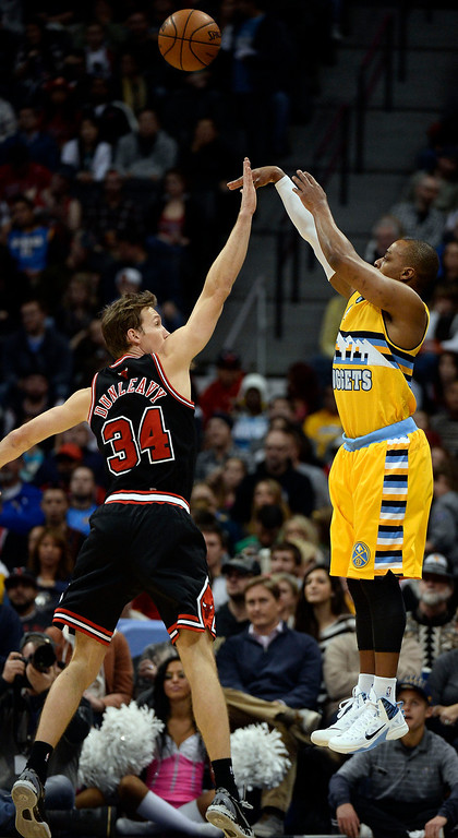 . Denver Nuggets shooting guard Randy Foye (4) takes a shot over Chicago Bulls small forward Mike Dunleavy (34) during the third quarter November 21, 2013 at Pepsi Center. (Photo by John Leyba/The Denver Post)