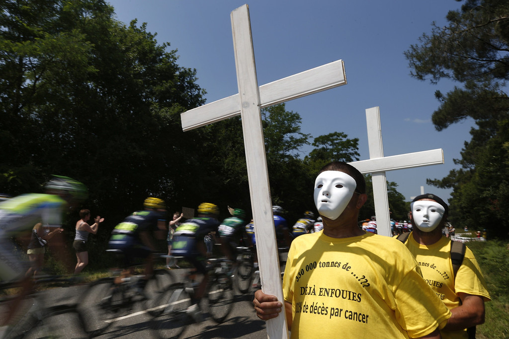 """. Inhabitants hold crosses as they protest along the road against waste landfill who \""""provoking cancers\"""" during the 197 km tenth stage of the 100th edition of the Tour de France cycling race on July 9, 2013 between Saint-Gildas-des-Bois and Saint-Malo, northwestern France.    JOEL SAGET/AFP/Getty Images"""
