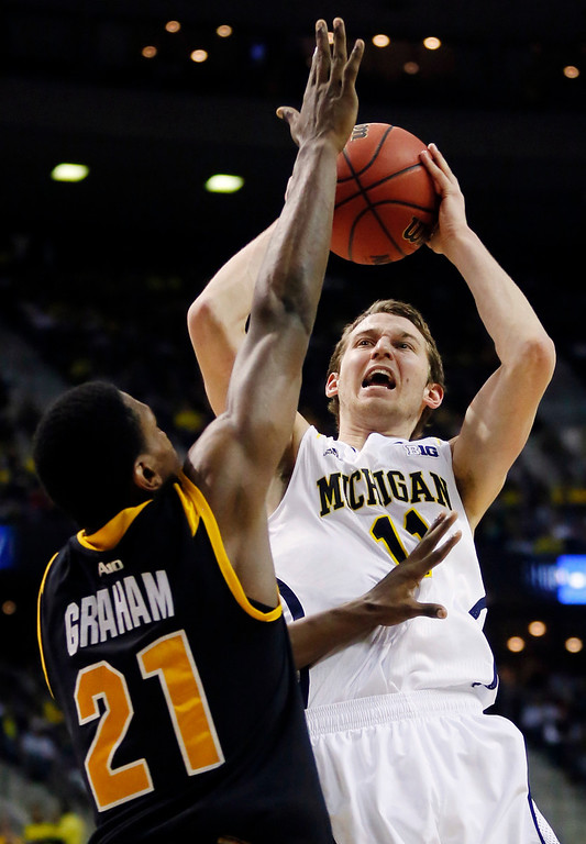 . Michigan guard Nik Stauskas (11) shoots against Virginia Commonwealth guard Treveon Graham (21) in the second half of a third-round game of the NCAA college basketball tournament, Saturday, March 23, 2013, in Auburn Hills, Mich. Michigan won 78-53. (AP Photo/Duane Burleson)