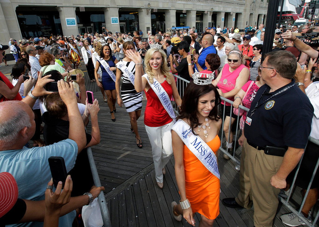 . Miss Rhode Island Jessica Marfeo waves as she follows Miss Puerto Rico Shenti Lauren as Miss America contestants arrive in Atlantic City, N.J. on Tuesday, Sept. 3, 2013. The Miss America pageant is back in the city where it began, six years after spurning the city for Las Vegas. The pageant held a welcoming ceremony Tuesday for the 53 contestants, one from each state plus the District of Columbia, Puerto Rico and the U.S. Virgin n Islands. The contestants filed out of Boardwalk Hall, where the competition will begin next week and culminate days later, and walked across the Boardwalk to a stage. (AP Photo/Mel Evans)
