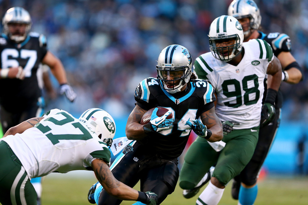 . Dee Milliner #27 of the New York Jets tries to stop  DeAngelo Williams #34 of the Carolina Panthers during their game at Bank of America Stadium on December 15, 2013 in Charlotte, North Carolina.  (Photo by Streeter Lecka/Getty Images)