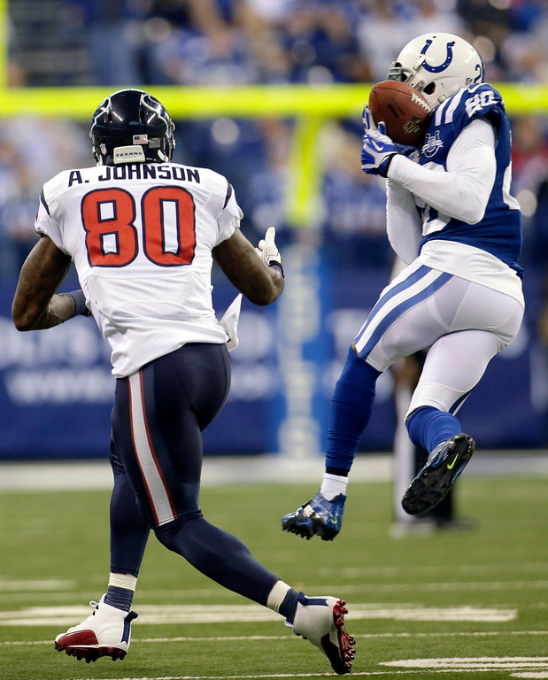 . Indianapolis Colts free safety Darius Butler, right, intercepts a pass intended for Houston Texans wide receiver Andre Johnson during the first half of an NFL football game in Indianapolis, Sunday, Dec. 15, 2013. (AP Photo/AJ Mast)