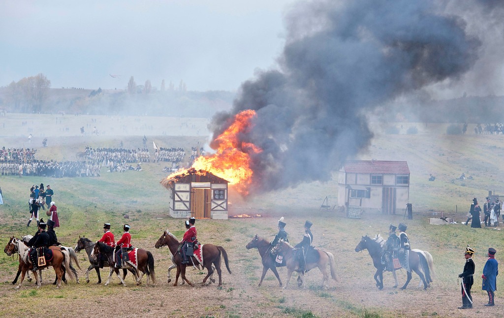 . Troops march in front of a burning house during the reconstruction of the Battle of the Nations at the 200th anniversary near Leipzig, central Germany, Sunday, Oct. 20, 2013. (AP Photo/Jens Meyer)