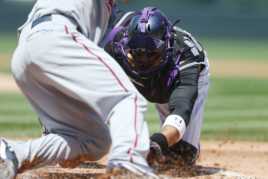 . Colorado Rockies catcher Wilin Rosario, back, tags out Minnesota Twins\' Brian Dozier at home plate on the back end of a double play hit into by Kendrys Morales in the first inning of an interleague baseball game in Denver on Sunday, July 13, 2014. (AP Photo/David Zalubowski)