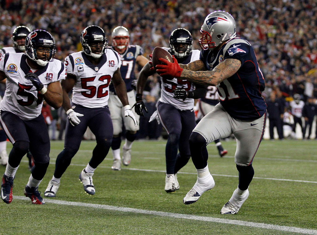 . New England Patriots tight end Aaron Hernandez scores a touchdown past Houston Texans linebackers Darryl Sharpton (51), Tim Dobbins (52) and Whitney Mercilus (59) during the first half of their NFL football game in Foxborough, Massachusetts December 10, 2012. REUTERS/Jessica Rinaldi