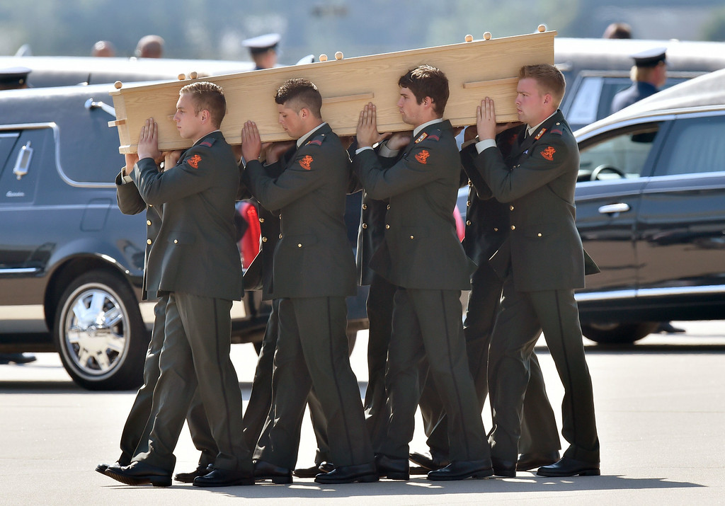 . Dutch military men carry coffins containing the remains of victims of downed Malaysia Airlines flight MH17, during a ceremony at Eindhoven Airbase on July 23, 2014, after a Hercules transport plane carrying the coffins landed from Ukraine. The first bodies from flight MH17 arrived in the Netherlands on July 23 almost a week after it was shot down over Ukraine, with grieving relatives and the king and queen of The Netherlands solemnly receiving the as yet unidentified victims. AFP PHOTO / JOHN  THYS/AFP/Getty Images