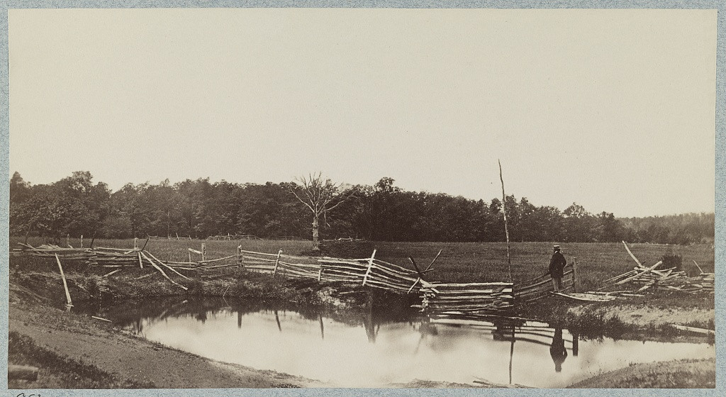 . The battle-field of Gettysburg. McPherson\'s woods in which Archer\'s (Confederate) Brigade was captured, view of the side towards the Chambersburg pike. Photograph shows photographer Mathew Brady standing in the field.  - Library of Congress Prints and Photographs Division Washington, D.C.
