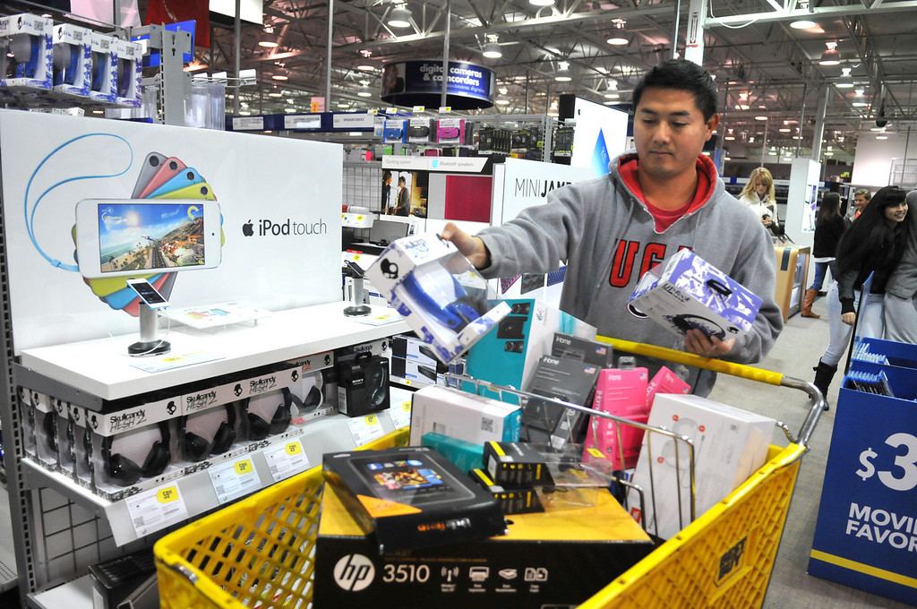 . Steven Doan picks up a few gifts at Best Buy in Savannah, Ga., during a very quiet Black Friday morning.  Doan, who often does most of his shopping online, decided to go out early Friday Nov. 29, 2013,  in hopes that he would avoid the big crowds that shopped when the stores opened Thanksgiving Day. (AP Photo/Savannah Morning News, Richard Burkhart)