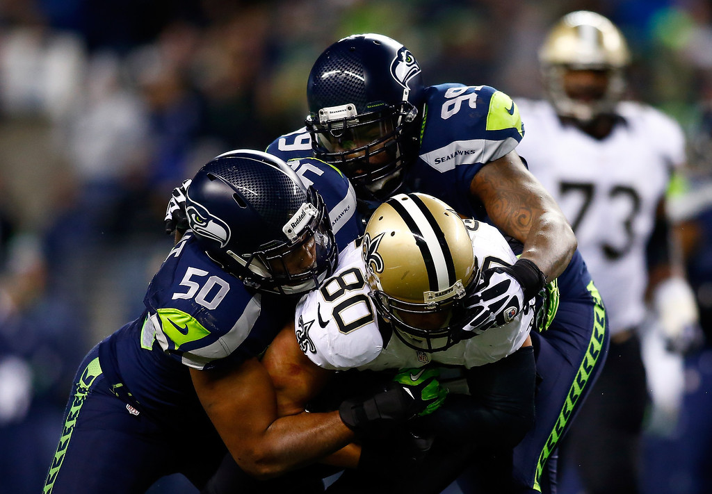 . Tight end Jimmy Graham #80 of the New Orleans Saints is tackled by outside linebacker K.J. Wright #50 and defensive tackle Tony McDaniel #99 of the Seattle Seahawks during a game at CenturyLink Field on December 2, 2013 in Seattle, Washington.  (Photo by Jonathan Ferrey/Getty Images)