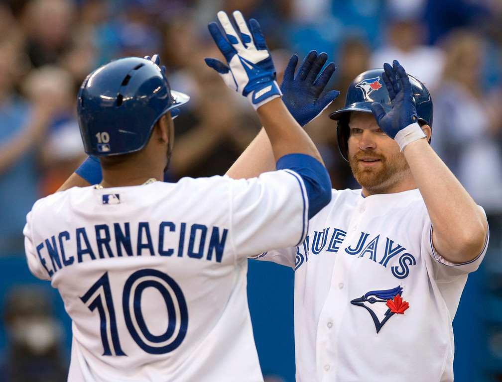 . Toronto Blue Jays Edwin Encarncacion congratulates teammate Adam Lind on his three-run home run during the first inning of a baseball game against the Colorado Rockies in Toronto on Wednesday, June 19, 2013. (AP Photo/The Canadian Press, Frank Gunn)