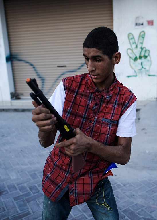 . A Bahraini man plays with a toy gun during the funeral of 10-year-old Ali Jaffer Habib, in the village of Malikiya, on August 10, 2013. Habib, according to his family, died after developing cancer due to the inhalation of tear gas fired by security forces earlier in the year. MOHAMMED AL-SHAIKH/AFP/Getty Images