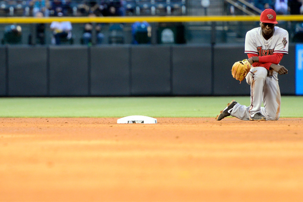 . DENVER, CO - MAY 21: Didi Gregorius (1) of the Arizona Diamondbacks kneels on the ground after attempting a circus throw, but was unable to get an out on Jhoulys Chacin (45) of the Colorado Rockies during action at Coors Field. The Arizona Diamondbacks visited the Colorado Rockies. (Photo by AAron Ontiveroz/The Denver Post)