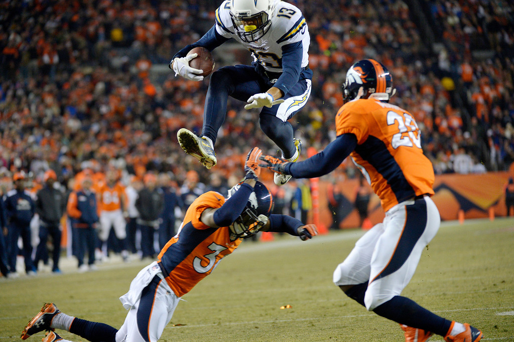 . San Diego Chargers wide receiver Keenan Allen (13) takes to the air and over Denver Broncos cornerback Kayvon Webster (36) and into Denver Broncos strong safety Mike Adams (20) on his way to a touchdown during the second quarter. The Denver Broncos vs. the San Diego Chargers at Sports Authority Field at Mile High in Denver on December 12, 2013. (Photo by Joe Amon/The Denver Post)