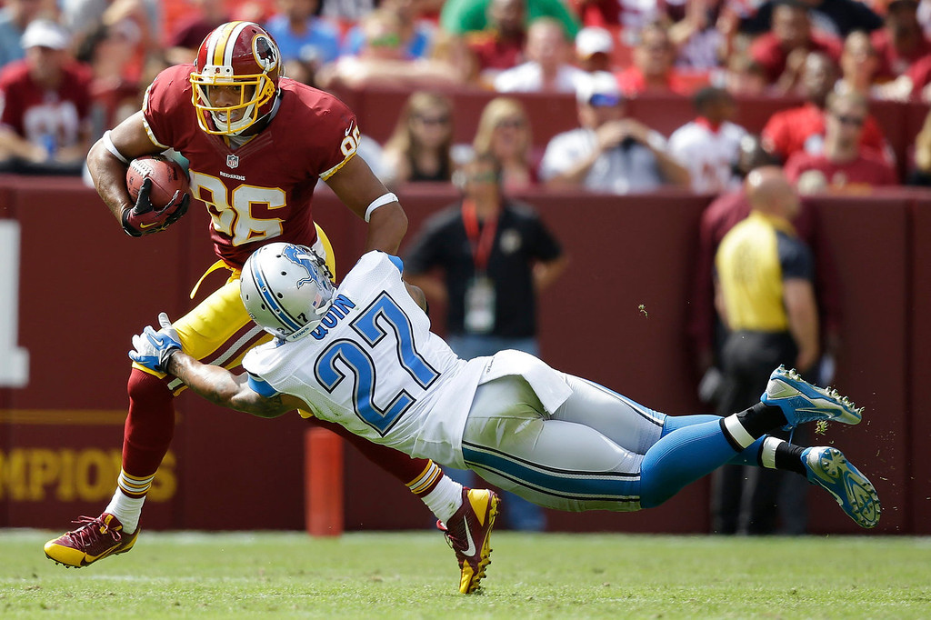 . Washington Redskins tight end Jordan Reed drags Detroit Lions strong safety Glover Quin with him during the first half of a NFL football game in Landover, Md., Sunday, Sept. 22, 2013. (AP Photo/Alex Brandon)
